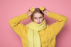 Human emotions. Blonde beautiful european girl in yellow sweater and scarf showing funny face, holding two sliced citrus. Human emotions. Blonde beautiful royalty free stock photos