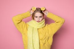 Human emotions. Blonde beautiful european girl in yellow sweater and scarf showing funny face, holding two sliced citrus. Human emotions. Blonde beautiful stock photography