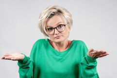 Puzzled hesitant woman shrugs shoulders expressing uncertainty. royalty free stock images
