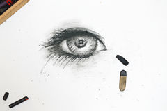 Human eye is drawn in charcoal on paper. Royalty Free Stock Photos