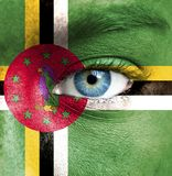 Human face painted with flag of Dominica stock image