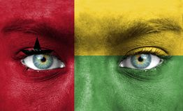 Human face painted with flag of Guinea-Bissau stock photo