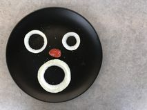 Human face on plate made from onion and grape tomato. Three pieces of onion and half of red grape tomato displayed on black plate looks like human face putted on Royalty Free Stock Images
