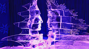 Human faces ice sculptures illuminated at night Stock Image