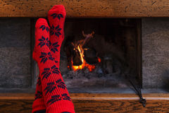 Human feet in red socks warming by fireplace Royalty Free Stock Image
