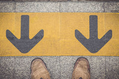 Human feet stand in front of arrow sign at train station Stock Photos