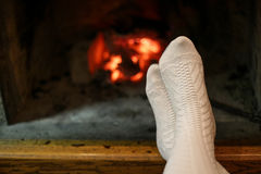 Human feet in wool socks warming by fireplace Stock Images