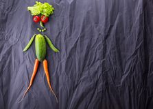 Human figure made of vegetables on black paper background. Weight loss and healthy lifestyle. With space for text.  royalty free stock images