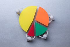 Human Figures Connecting Pieces Of Pie Chart. Elevated View Of Human Figures Connecting Pieces Of Multicolored Pie Chart On Grey Background stock photos