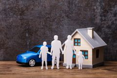 Human Figures Standing In Front Of House And Blue Car. On Wooden Plank stock photography