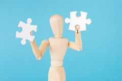 Human figurine hold white puzzle pieces Royalty Free Stock Image