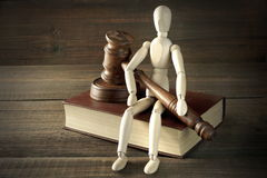 Human Figurine With Judges  Or Auctioneer  Gavel Sit On  Book. Wooden Human Figurine With  Judges Or  Auctioneer Gavel In Hand Sit On Red Book On The Rough And Stock Photos