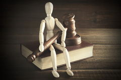 Human Figurine With Judges  Or Auctioneer  Gavel Sit On  Book. Wooden Human Figurine With  Judges Or  Auctioneer Gavel In Hand Sit On Red Book On The Rough And Royalty Free Stock Images