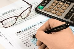 Human fills out the tax form stock images