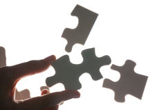 Human finger holding puzzle Stock Photo
