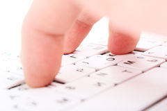 Human finger on a laptop keyboard. Press a key Stock Image
