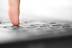Human finger pressing button on laptop computer Royalty Free Stock Image