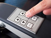 Human finger pressing push buttons on the armrest Stock Photos