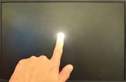 Human finger touching on computer screen and light Stock Image