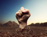 Human fist bursts through the ground Stock Images