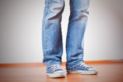 Human foot with jeans and sneakers Stock Images