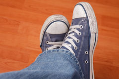 Human foot with jeans and sneakers Royalty Free Stock Image