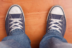 Human foot with jeans and sneakers Stock Photography