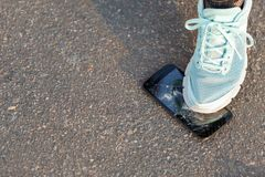 The human foot r comes on the broken screen of a smartphone on the asphalt. royalty free stock photo