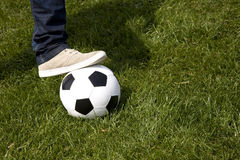 Human foot and a soccer ball Royalty Free Stock Images
