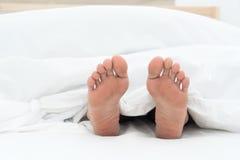 Human foot under bed sheet Royalty Free Stock Photo