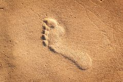 Human footprint on the beach sand. Memories of the sea. Greetings from vacation. Evening on the beach. Human footprint on the beach sand. Memories of the sea Royalty Free Stock Photography