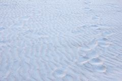 Human footprints of bare feet on textured sand. Snow Stock Photography