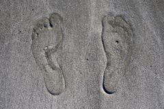Human footprints on beach sand, close up royalty free stock photography