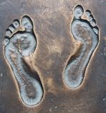Human footprints on the bronze. Royalty Free Stock Photo