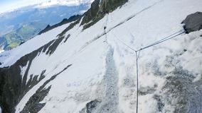 Human footprints on a Couloir passage ridge of Alps snowy mountains Stock Photo