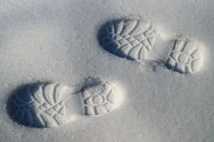 Human footprints boots reflected on the white snow in winter stock photo