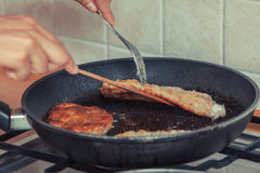 Human frying breaded chicken cutlet. Stock Photo