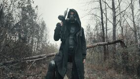 Human of future. Woman in hooded mantle and gas mask standing in forest. Dystopian stalker concept, female survivor