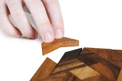 Human hand assembling wooden square puzzle Royalty Free Stock Images