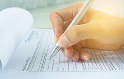 Human hand with ballpoint pen over application form.  stock image