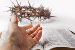 Human hand on bible. Holy bible with human hand and crown of thorns isolated on white Royalty Free Stock Photo