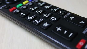 Human hand changes the channels on the TV remote control. Female hand presses the switch button on the black remote control from the TV on a white background stock video footage