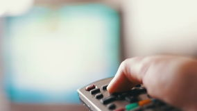 Human hand changes the channels on the TV remote control. Hand presses buttons on remote control and switches off TV,human hand changes the channels on the TV stock footage