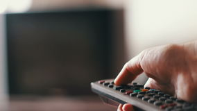Human hand changes the channels on the TV remote control. Hand presses buttons on remote control and switches off TV,human hand changes the channels on the TV stock video footage