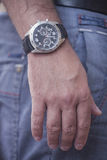 Hand of the clock. Human hand with a clock on the background of his jeans Stock Image