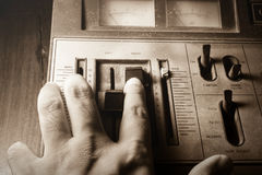 Human hand controlling radio sound,sepia filtered. Royalty Free Stock Images