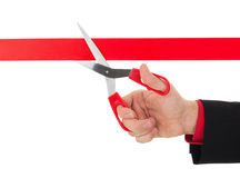 Human hand cutting the red ribbon with scissors Royalty Free Stock Photography