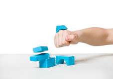 Human hand destroying house made of wooden blocks Stock Photos