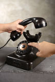 Human hand dialing numbers on antique telephone. Over abstract background Stock Images