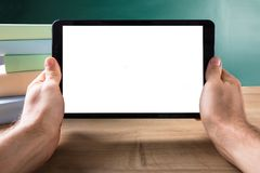 Human Hand With Digital Tablet Showing Blank White Screen. In Front Of Blackboard Royalty Free Stock Photo